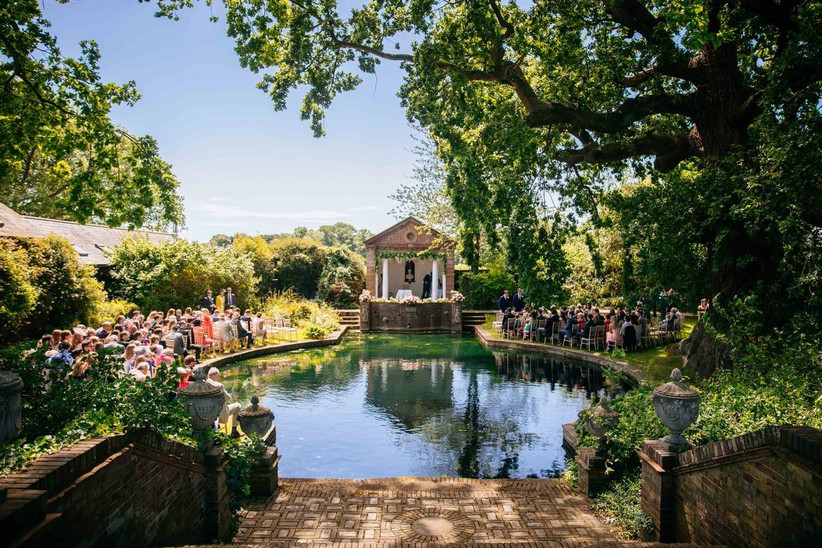 Outside ceremony by a pond in a garden
