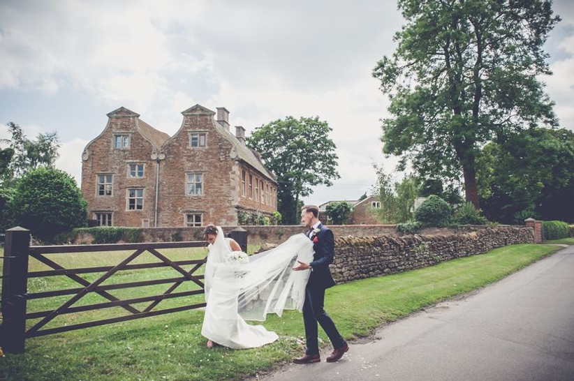 Groom holds up a bride's wedding dress train as they walk outside a manor house