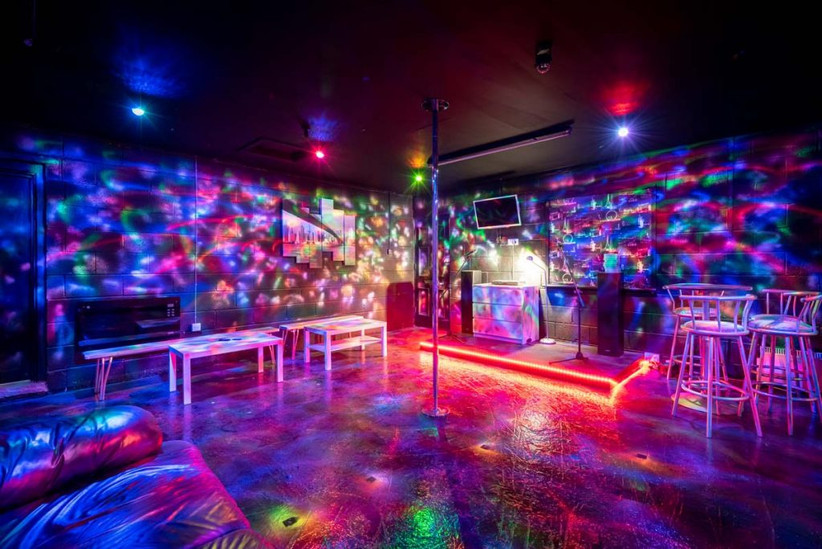 Disco room with colourful lights and dancing pole
