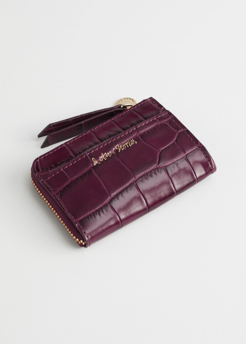 Burgundy leather mini wallet embossed with a gold logo against a white background