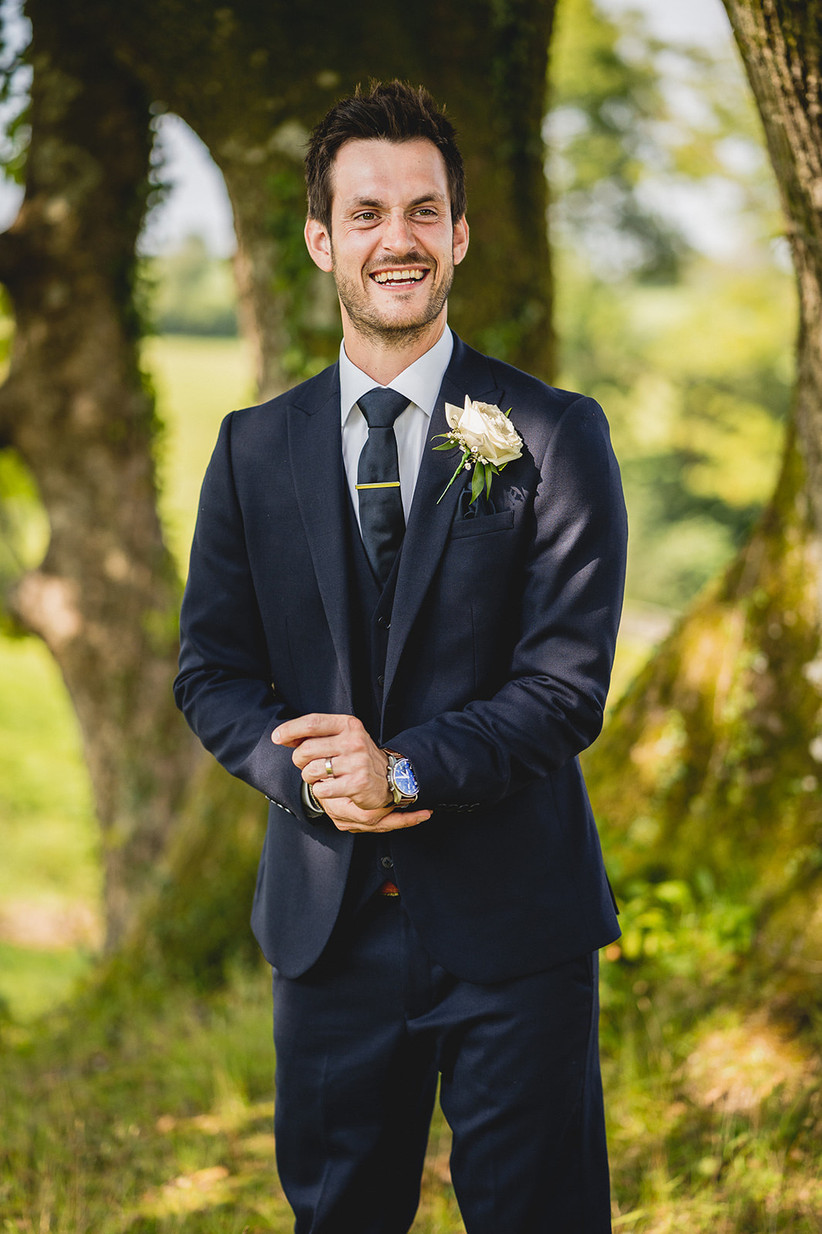 Groom in a navy suit posing for a picture