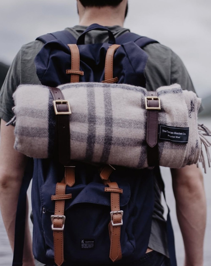 Picture of man from behind wearing a navy backpack with a neutral tartan blanket rolled at the top