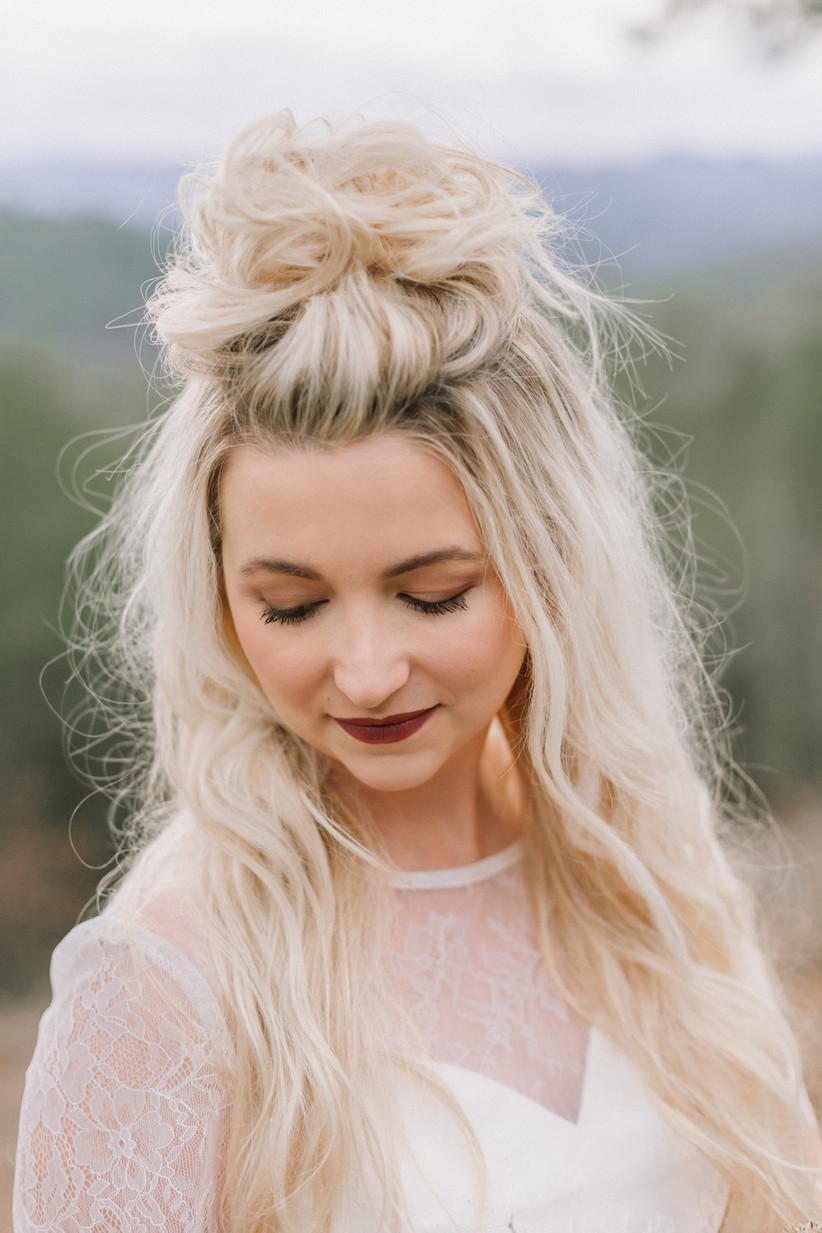 Half up half down hairstyle with a volumised top knot
