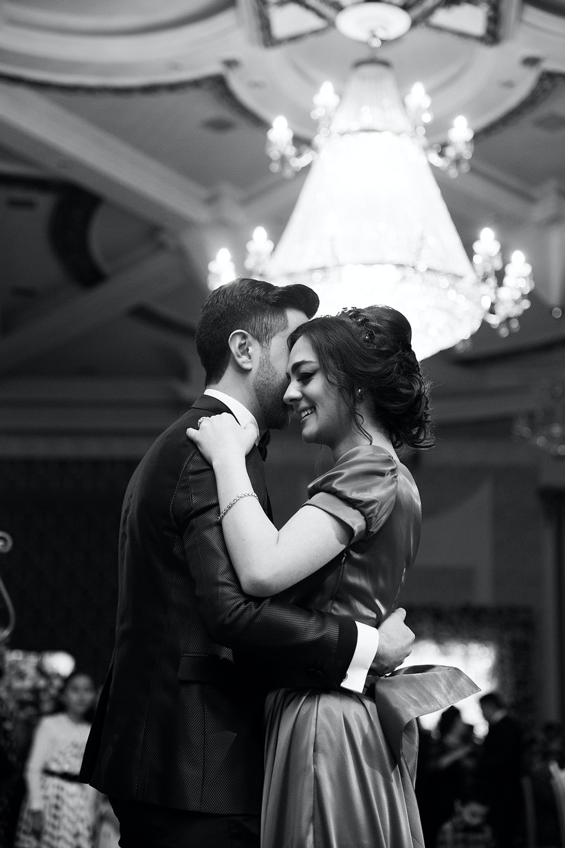 Man and woman in formalwear dancing and smiling beneath a chandelier on a dance floor