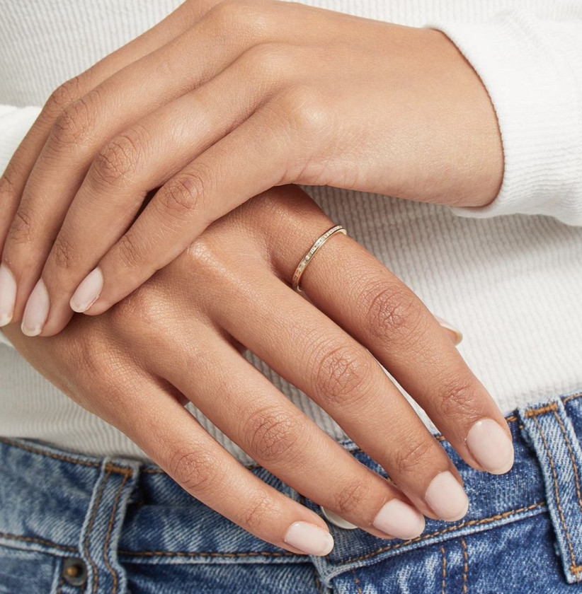 Woman wearing a white top and blue jeans crossing her hands in front of her with a slim silver band featuring baguette cut diamonds on the first finger of her left hand