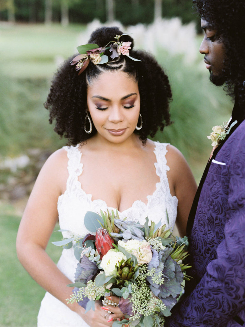Bride standing next to a groom with a floral headband and ombre eyeshadow