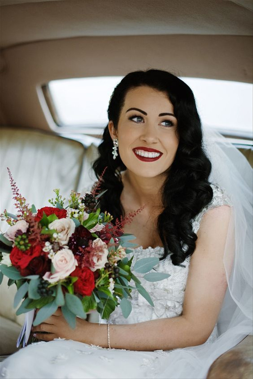 Bride with a red lip sitting in a car holding a bouquet