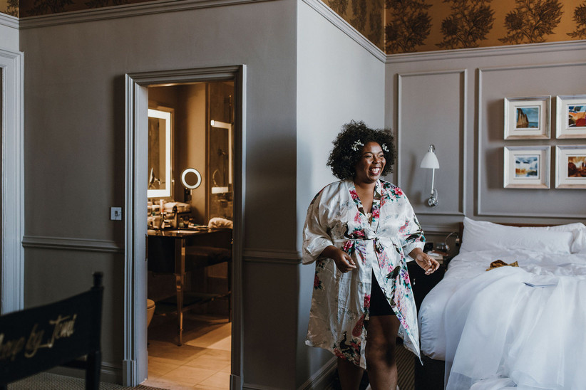 Michelle in a floral robe in a hotel room, laughing