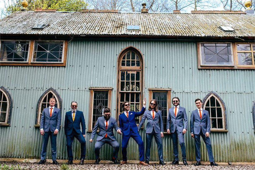 Groomsmen in blue suits with red ties standing outside a building