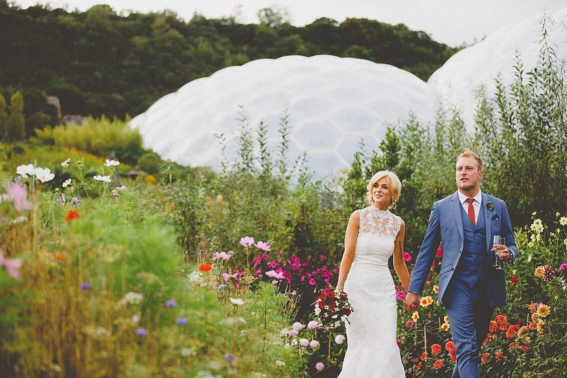 Bride and groom outside the Eden Project biome, surrounded by flowers