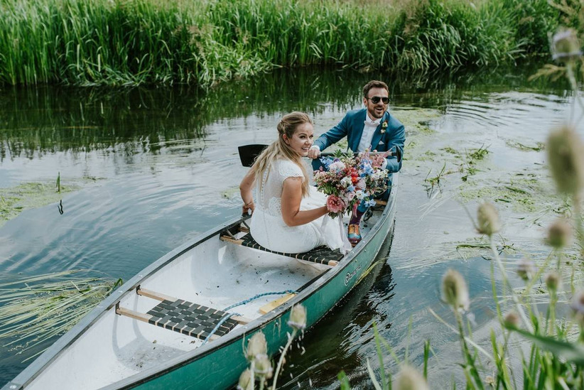 Bride and groom in a canoe laughing in a river