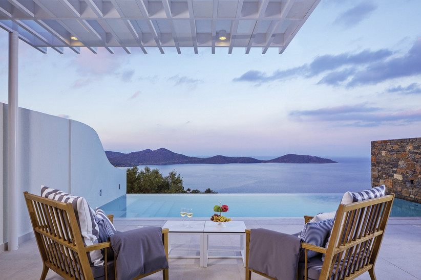 Two sun loungers overlooking an infinity pool in Crete