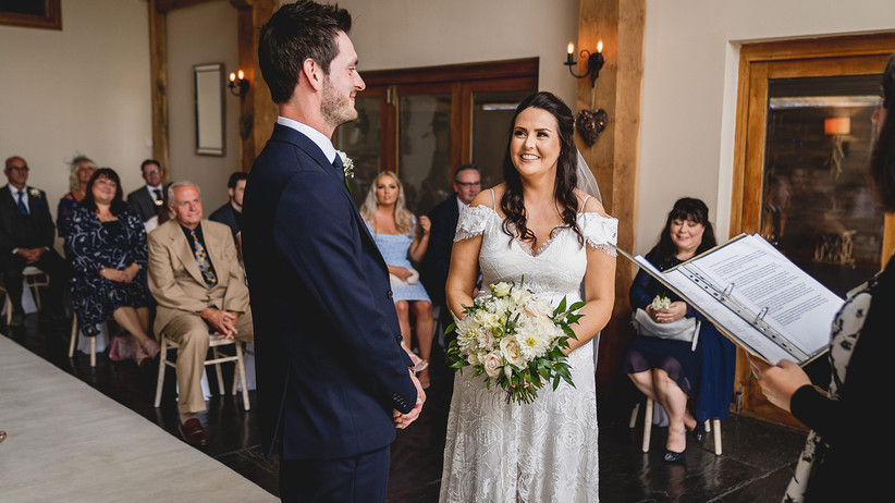 Bride and groom smile at each other during their wedding ceremony