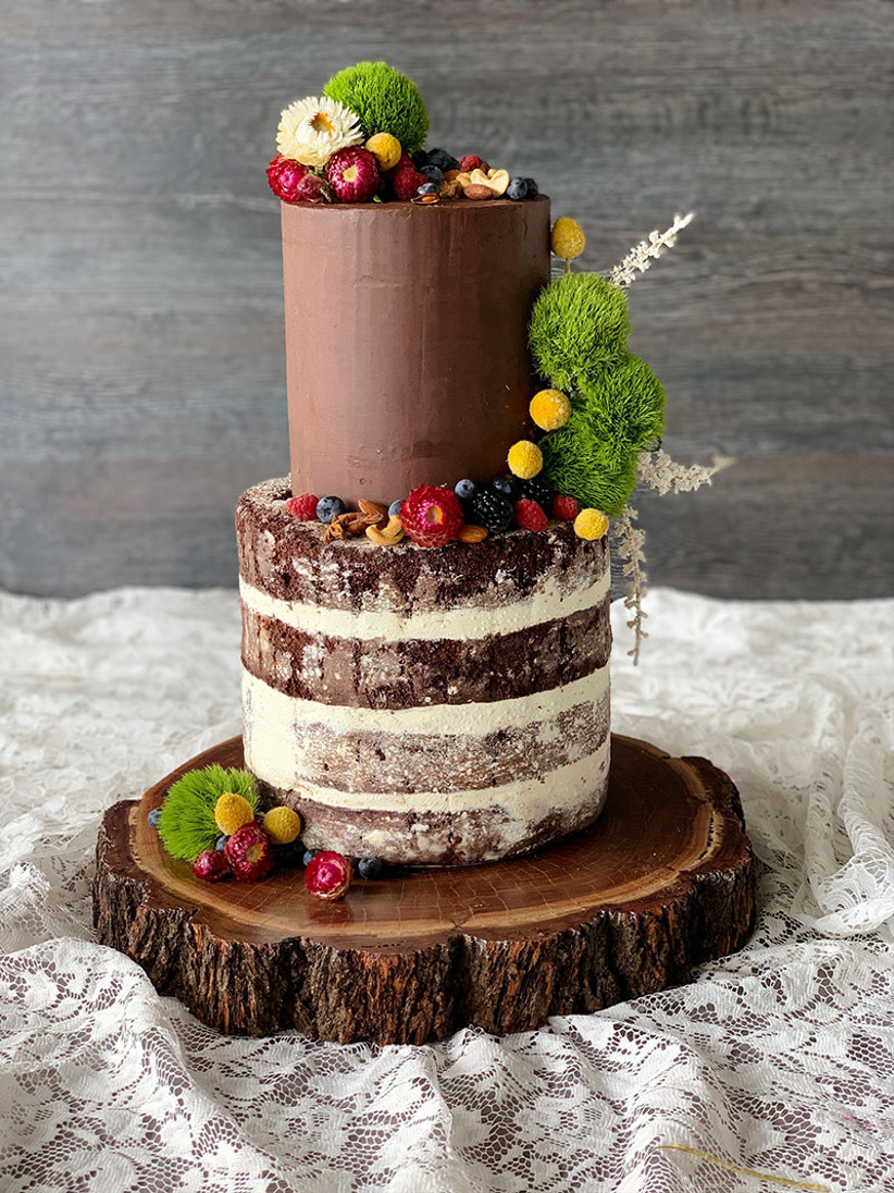 Two tiered chocolate rustic wedding cake with bright flowers and fruit