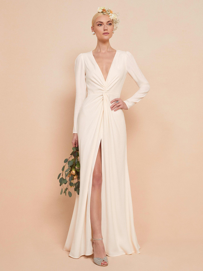 Model wearing a leg split long sleeved wedding dress