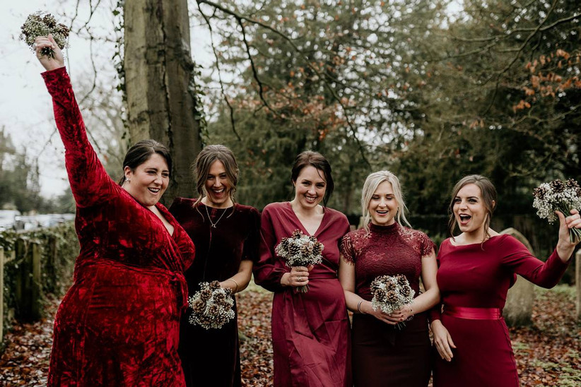 Bridesmaids wearing mismatched maroon dresses