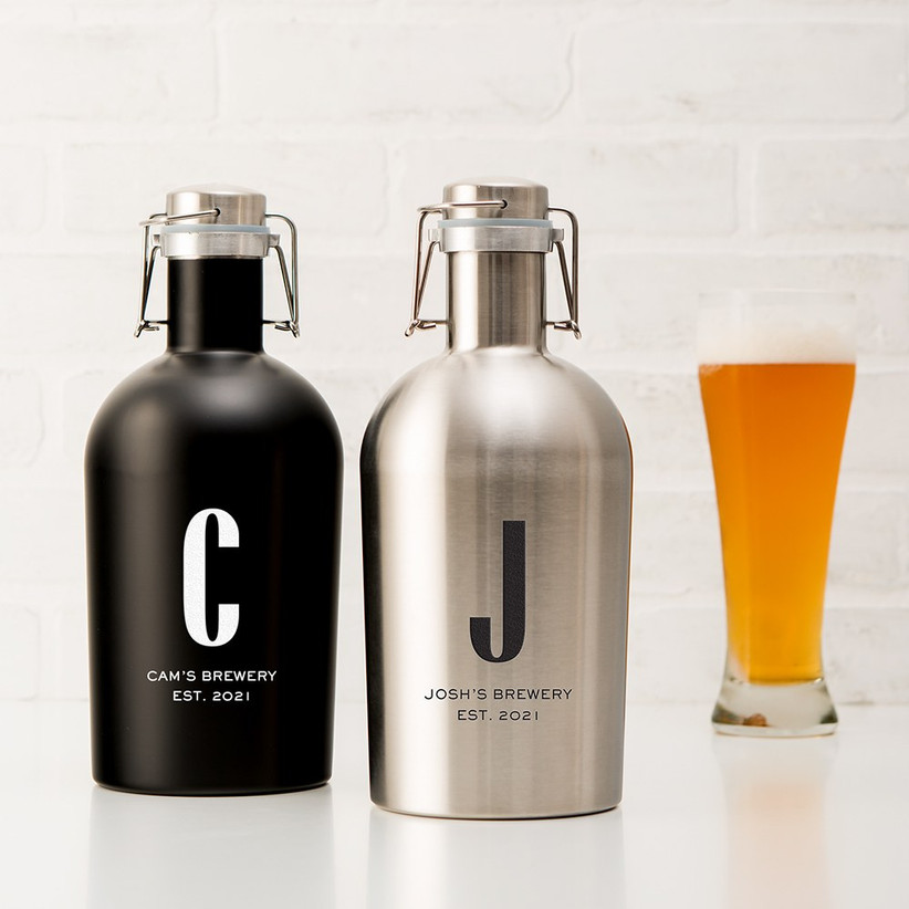 Personalised black and stainless steel beer growlers next to a full tall glass of beer