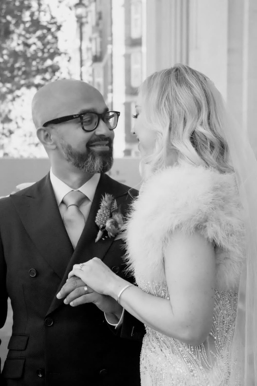 Black and white photo of a brown skinned groom with black glasses and a dark suit smiling at his blonde haired white bride who's wearing a cream fur stole and beaded ivory wedding dress