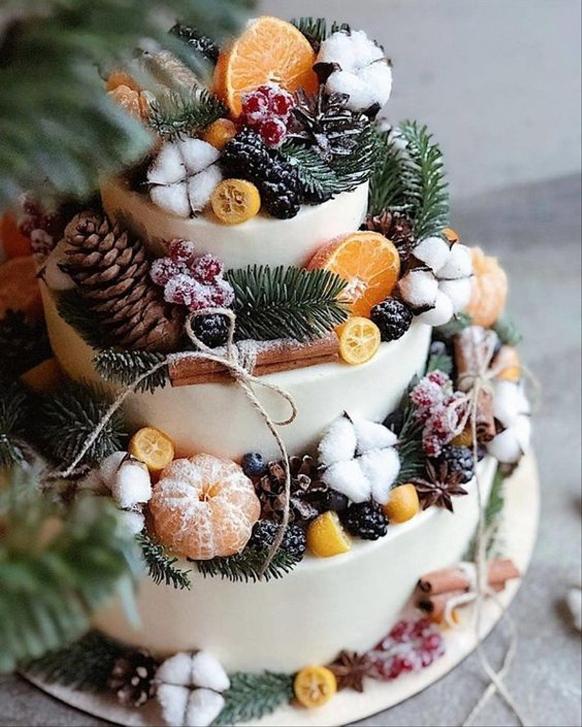 Three tiered rustic wedding cake with frosted berries, pinecones, fruit and cinnamon sticks
