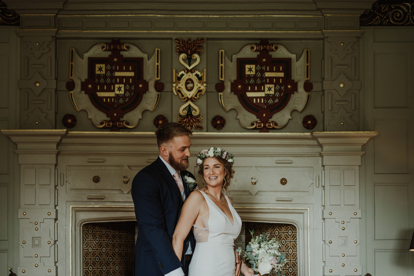 Katherine and David in front of a fireplace at Elmore Court