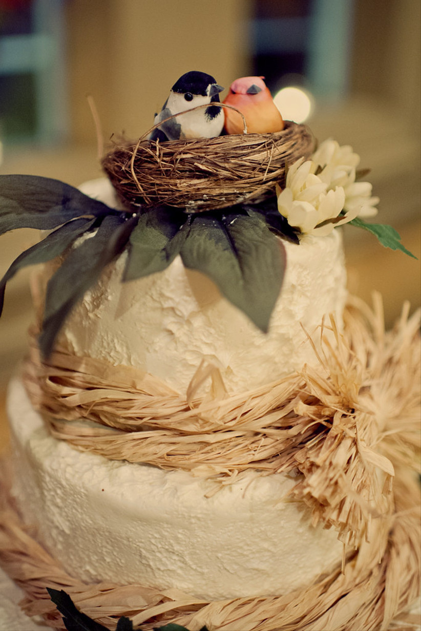 White rustic wedding cake with straw and bird's nest topper