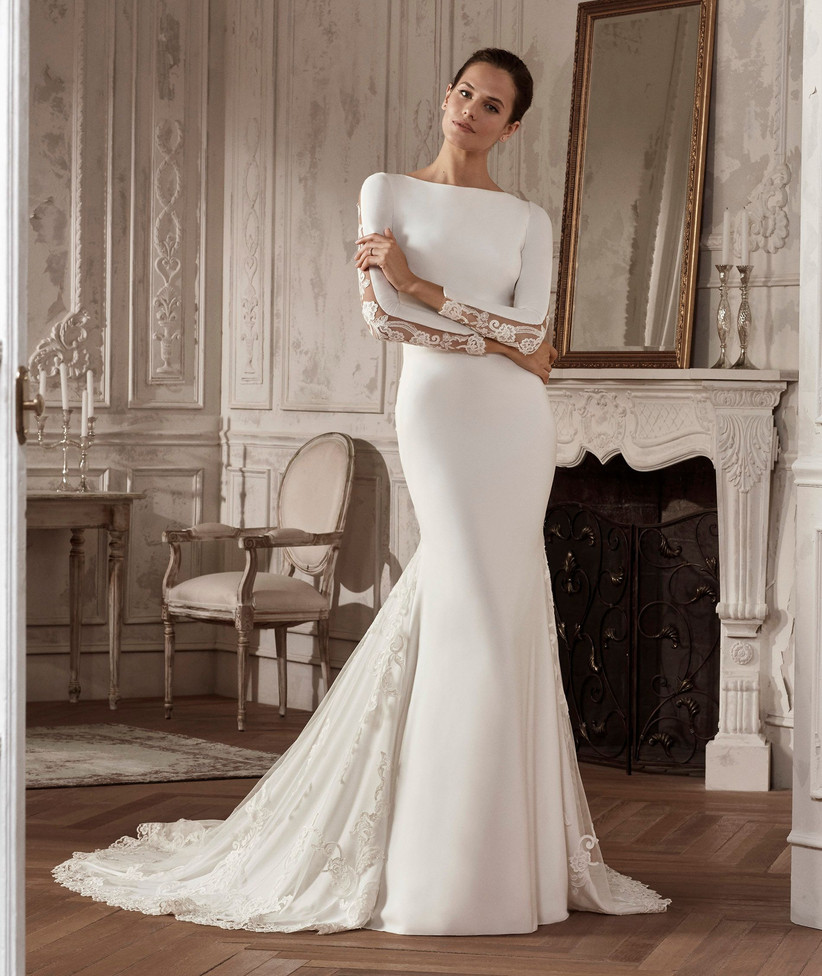 Model wearing a cut out panel long sleeved wedding dress