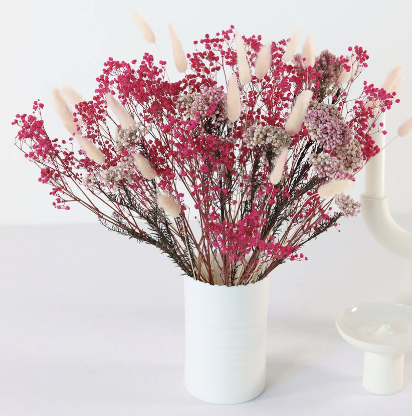 A white vase containing a colour bunch of pink and white dried flowers