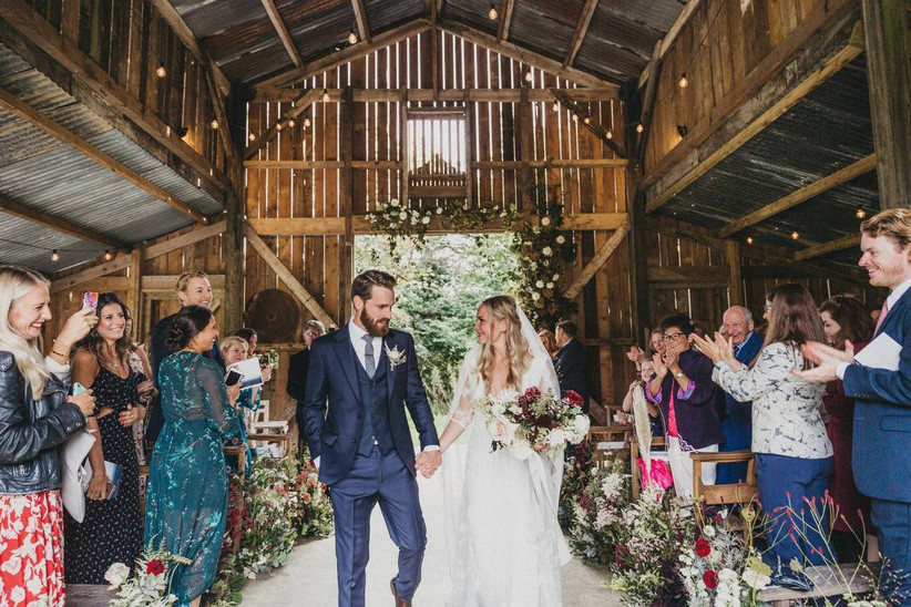 Rustic barn wedding ceremony with bride, groom and wedding guests