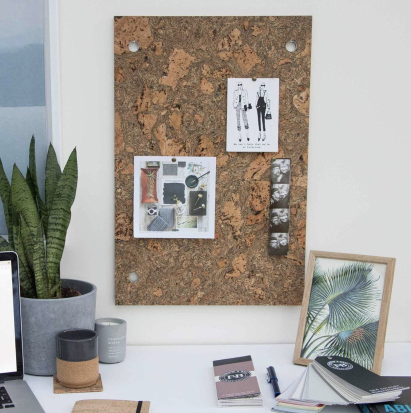 A marbled cork board with artwork and polaroid photos pinned to it next to a green plant and working desk with notebooks, a laptop and a candle