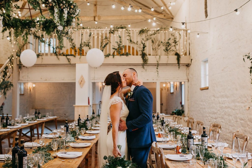Couple kissing inside Wyresdale Park barn, which has white brick walls