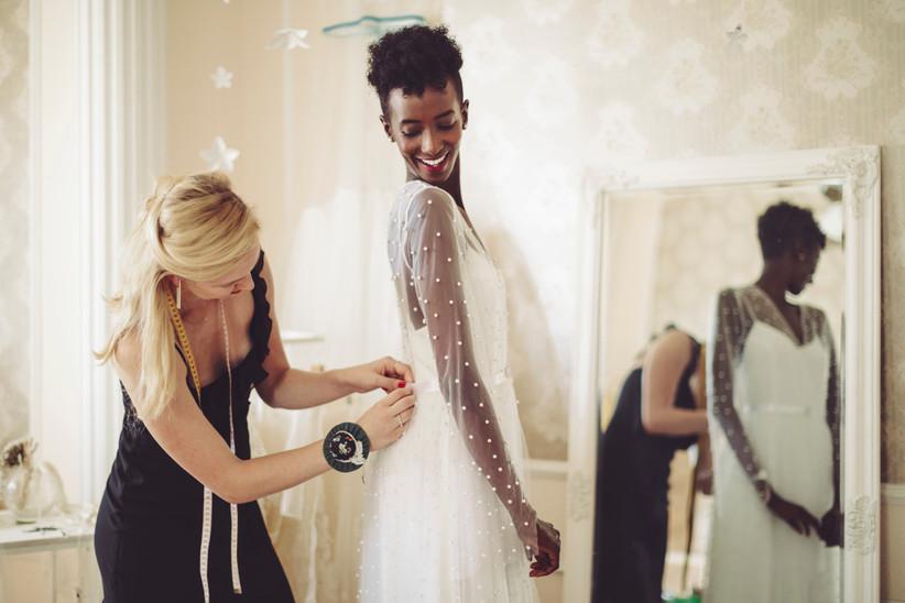 Fashion designer is adjusting the wedding dress