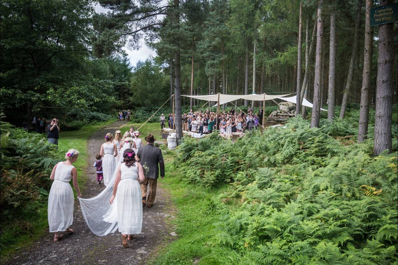 guests walking up to a gazebo for a woodland wedding ceremony