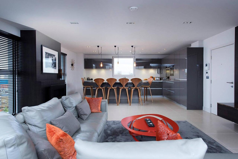 Apartment living area with grey sofas and open plan kitchen with orange details