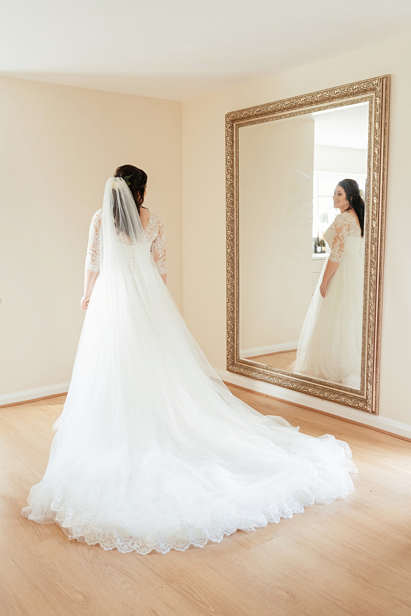 Becky looking at herself in a full length mirror wearing a white wedding dress and a veil