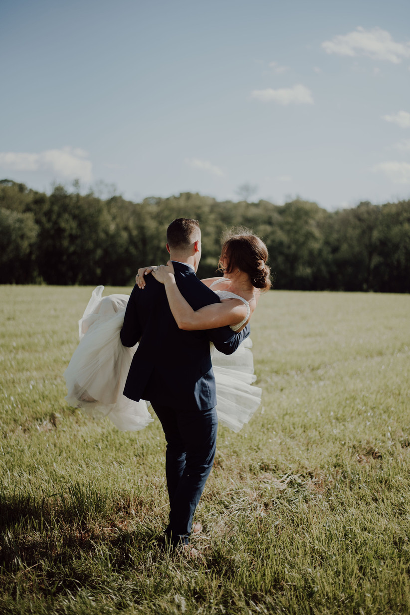 Groom carrying laughing bride through a green field