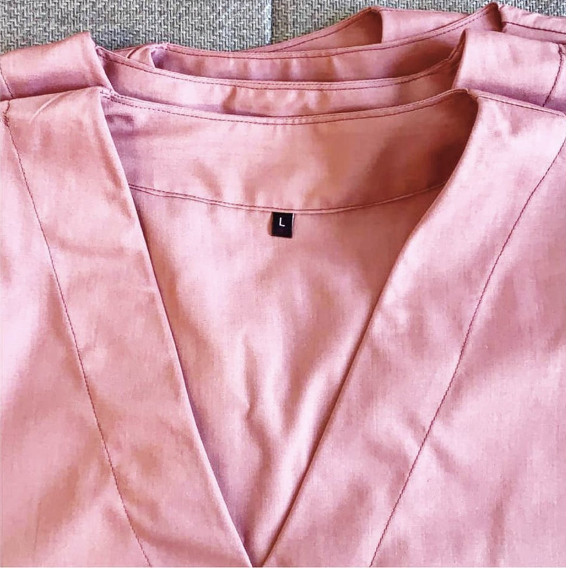 Folded light pink large scrubs on a grey carpet