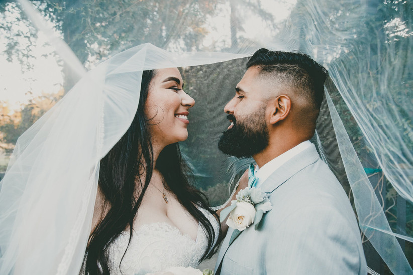 Indian couple in a white wedding dress and light blue wedding suit smiling at each other under a sheer bridal veil