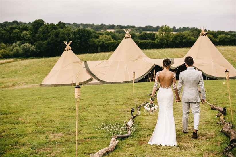 Bride and groom hold hands walking towards a wedding tipi