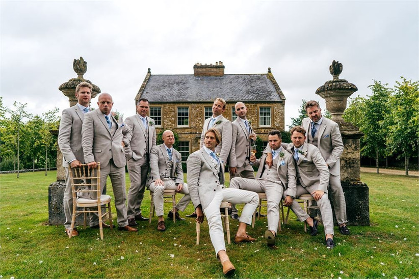 Groomsmen in beige suits sitting for a group photo outside a house
