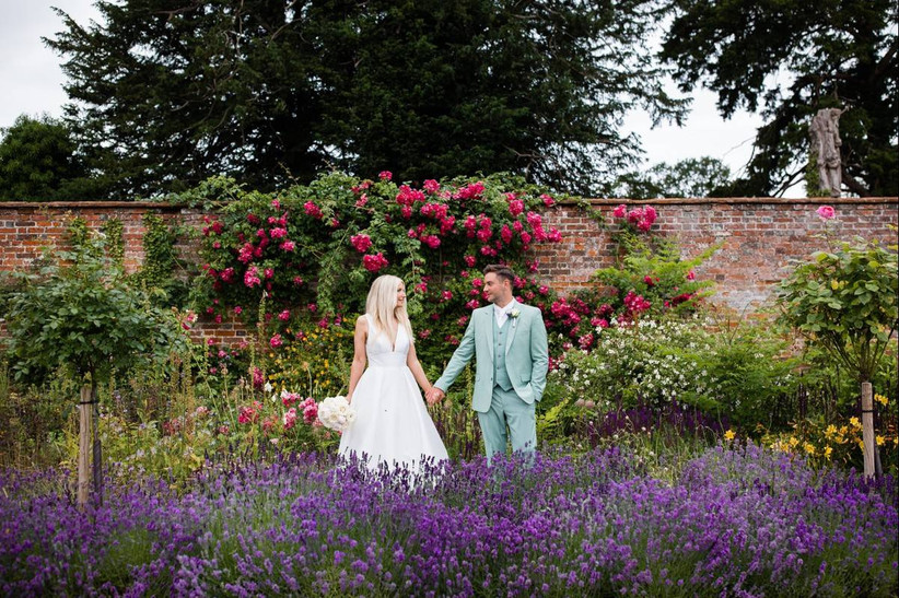 Bride and groom holding hands in a flower garden