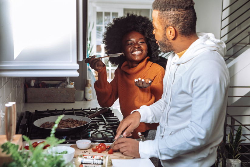 Couple cooking and laughing together in front of a hob