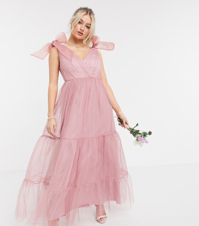 Girl wearing a pink tulle bridesmaid dress holding a rose