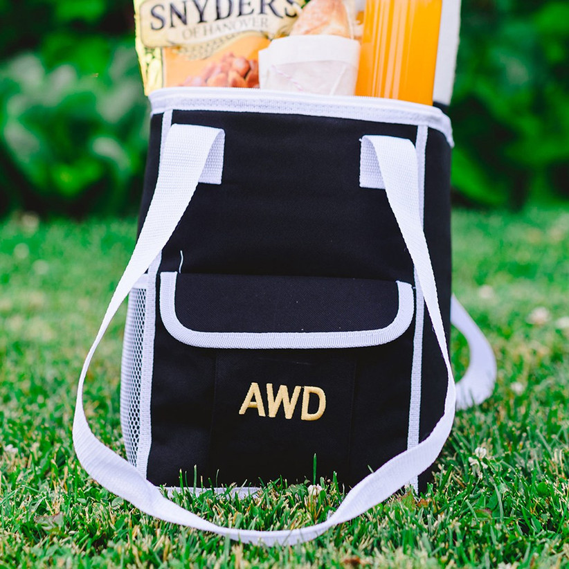 Black cool bag with three golden initials on the front and white handles resting on a grass lawn