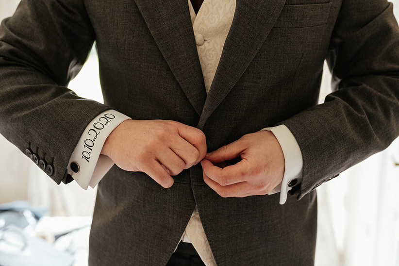 Ben doing up his grey suit jacket. He has the couple's wedding date written in black on the cuff of his white shirt