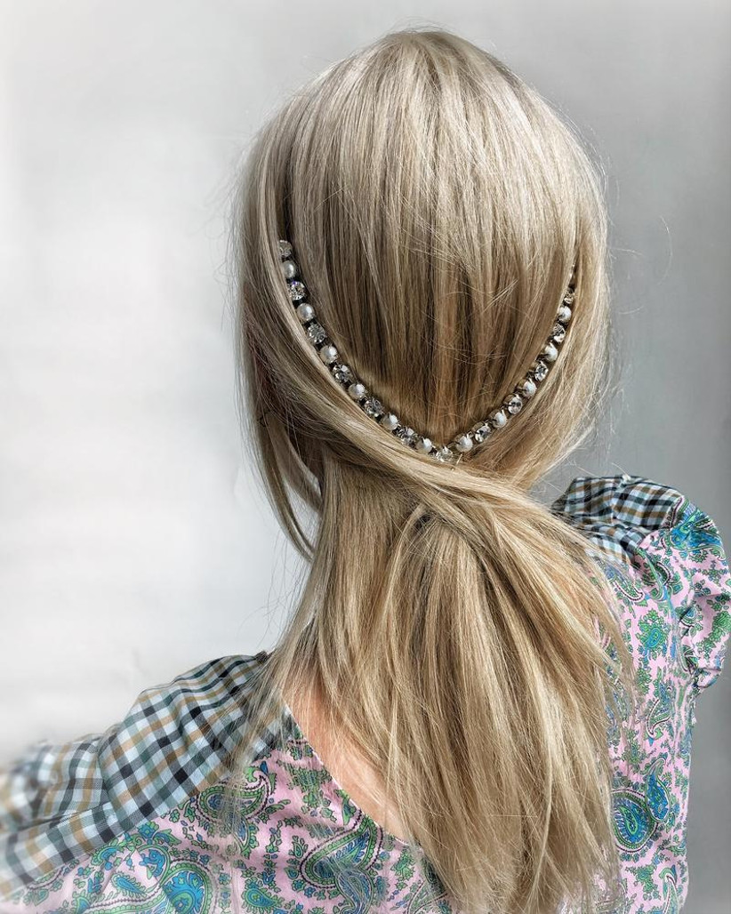 Straight cross over half up half down hairstyle with an embellished chain