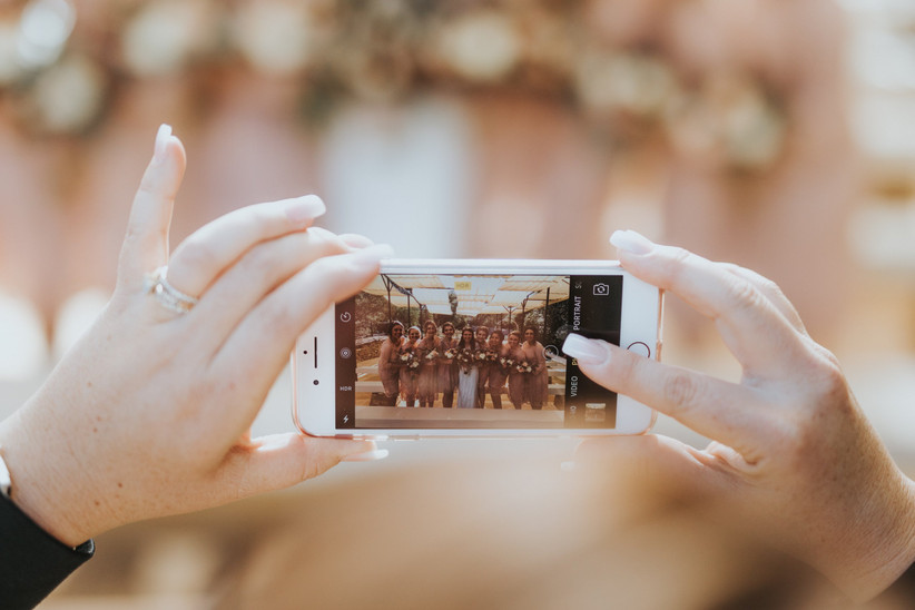 Woman holding an iPhone as she takes a picture of a bride and her bridesmaids