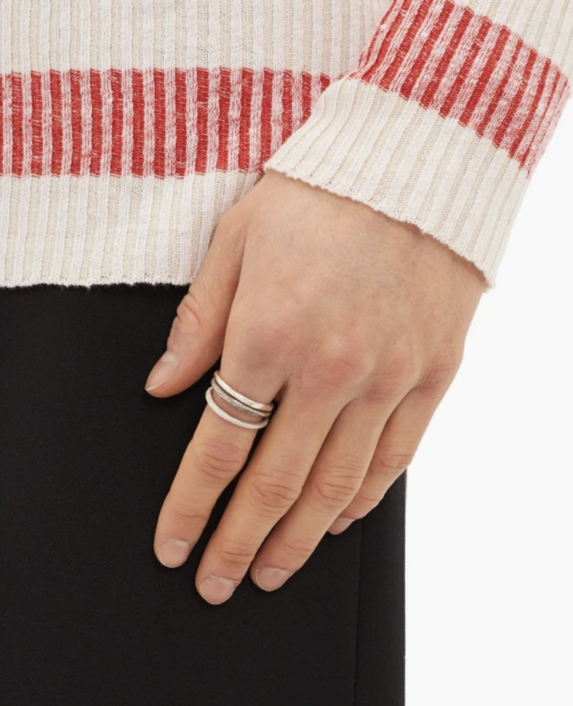 Man in a stripy red and white jumper wearing a triple layered silver ring on his first finger