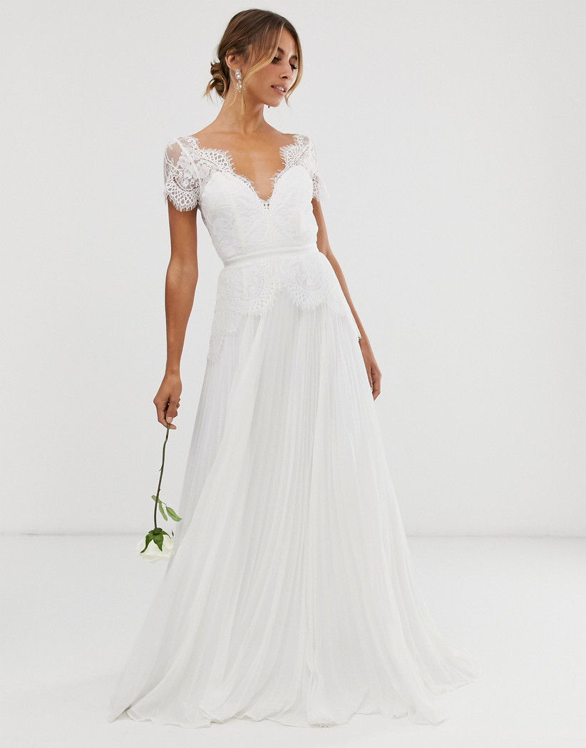 Girl wearing a lace scalloped sleeve wedding dress holding a white rose