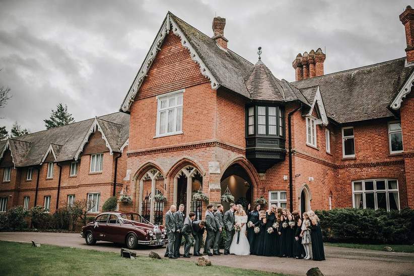 Wedding party stand outside a country house