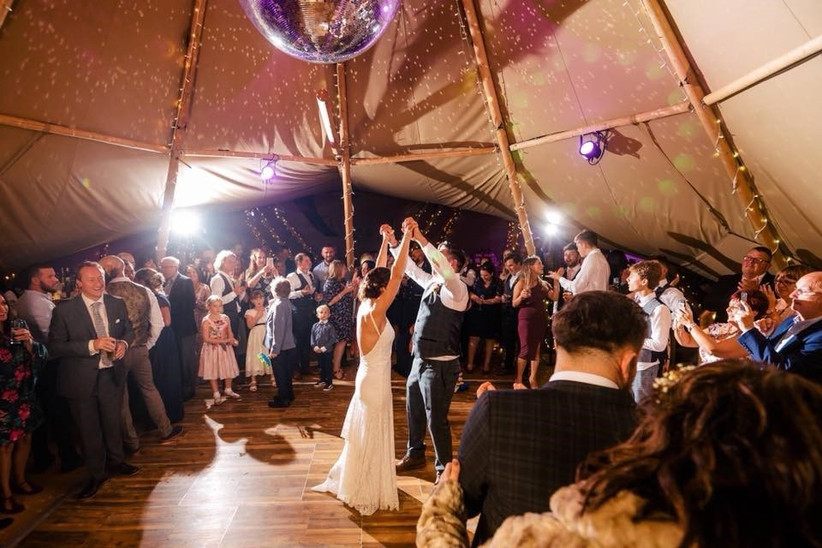 Wedding guests dance in a tipi with a disco ball